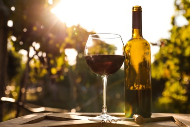 Bottle and glass of red wine on wooden table in vineyard