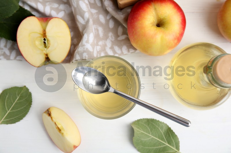 Natural apple vinegar and fresh fruits on white wooden table, flat lay
