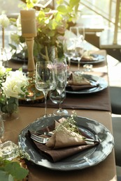 Festive table setting with beautiful tableware and floral decor in restaurant