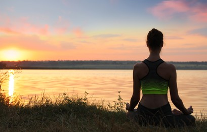 Woman meditating near river at sunset, back view. Space for text