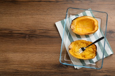 Halves of cooked spaghetti squash in baking dish on wooden table, top view Space for text