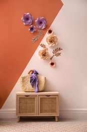 Cabinet near color wall with floral decor indoors