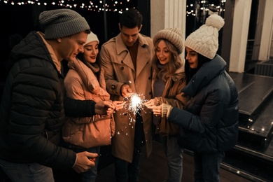 Group of people holding burning sparklers outdoors