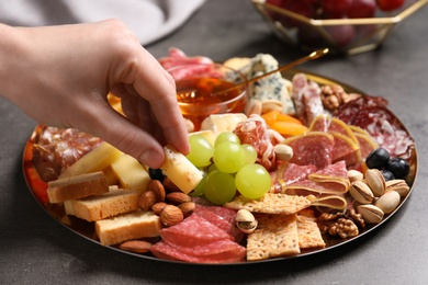 Woman taking cheese from plate with different appetizers on grey table, closeup