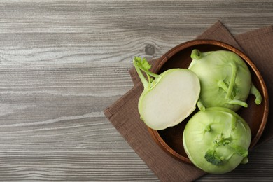 Whole and cut kohlrabi plants on wooden table, top view. Space for text