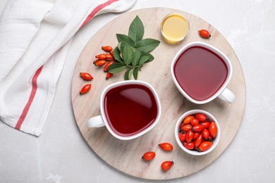 Fresh rose hip tea and berries on light table, flat lay