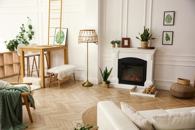 Elegant artificial fireplace and logs in room. Interior design