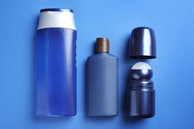 Shower gel, shampoo and roller deodorant on blue background, flat lay. Men's cosmetics