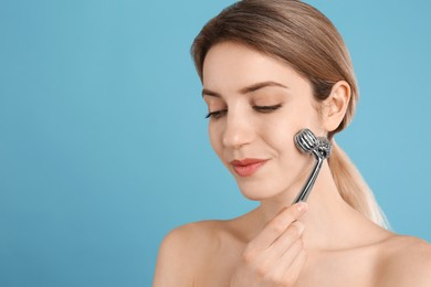 Young woman using metal face roller on light blue background, space for text