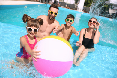 Happy family having fun in swimming pool