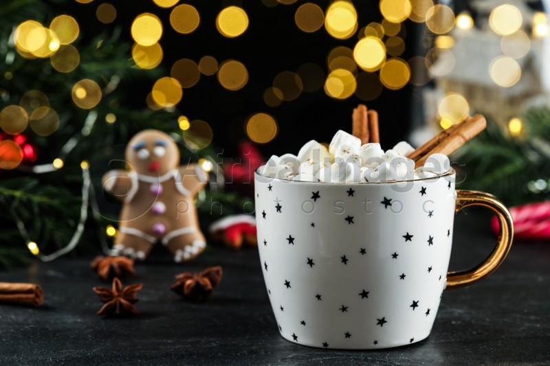 Delicious hot chocolate with marshmallows and cinnamon near Christmas decor on black table against blurred lights, space for text