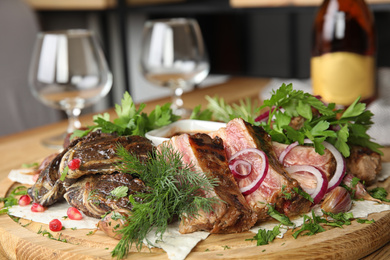 Delicious roasted ribs and liver with herbal on wooden board, closeup