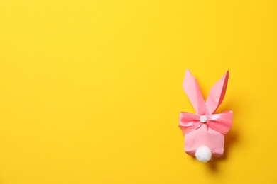 Creative Easter bunny gift bag on color background, top view with space for text