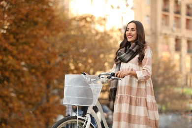 Beautiful happy woman with bicycle on city street