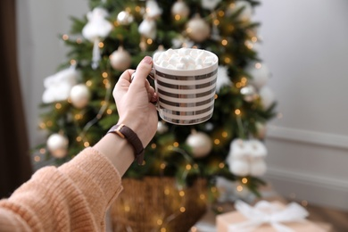 Woman with cup of delicious hot drink near Christmas tree at home, closeup
