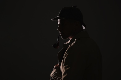 Old fashioned detective with smoking pipe on dark background. Space for text