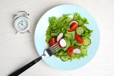 Alarm clock and plate with salad on white wooden  table, flat lay. Meal timing concept