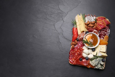 Different delicious snacks on black table, top view. Space for text