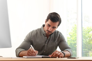 Handsome young man working with notebook at table in office