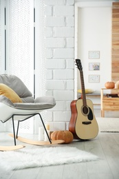 Cozy room interior with rocking chair, guitar and autumn decor