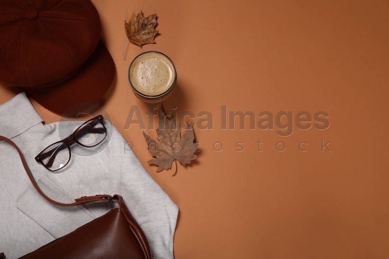 Flat lay composition with stylish hat and coffee on orange background, space for text