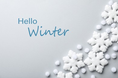 Beautiful snowflakes, decorative balls and phrase Hello Winter on light background, flat lay