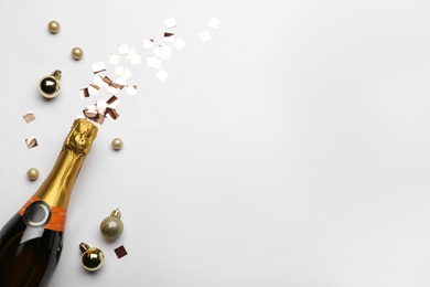 Flat lay composition with confetti, festive decor and bottle of champagne on light background. Space for text