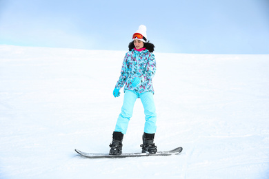 Young woman snowboarding on hill at mountain resort. Winter vacation