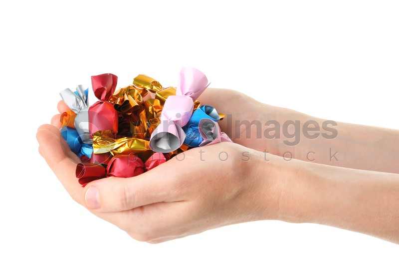 Woman holding heap of candies in colorful wrappers isolated on white, closeup