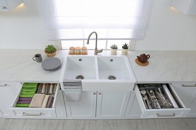 Open drawers with different utensils, towels and napkins in kitchen, above view
