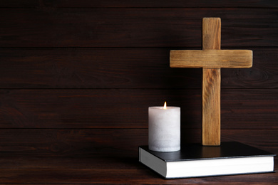 Cross, Bible and burning candle on wooden background, space for text. Christian religion