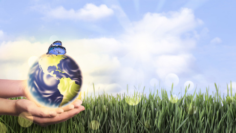 Woman holding Earth with butterfly outdoors, closeup