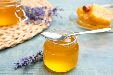 Tasty honey in glass jar and lavender flowers on light blue wooden table