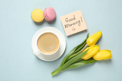 Delicious coffee, macarons, flowers and card with GOOD MORNING wish on light background, flat lay