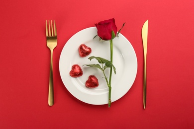 Beautiful table setting for Valentine's Day dinner on red background, flat lay.