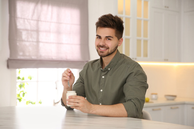 Happy young man with tasty yogurt at table in kitchen