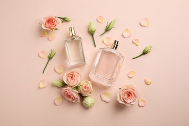 Flat lay composition with different perfume bottles and fresh flowers on beige background