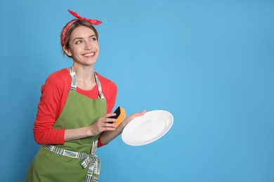Young housewife with plate and sponge on light blue background. Space for text