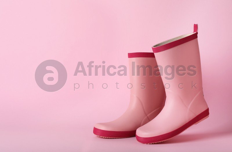 Pair of rubber boots on pink background, space for text