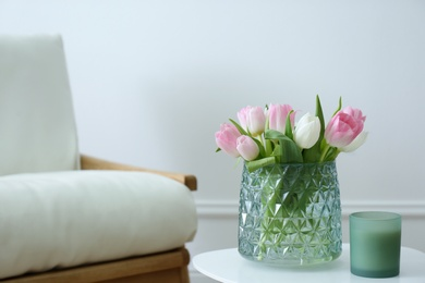 Vase with beautiful tulips and candle on table indoors, space for text. Interior elements