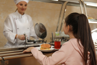 Little girl with plastic tray near serving line in canteen. School food