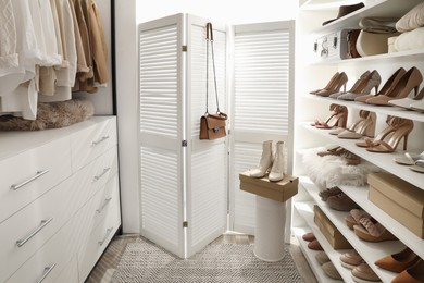 Dressing room interior with clothes rack and collection of stylish shoes