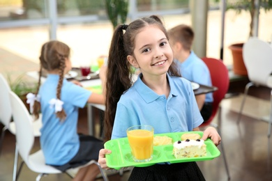 Cute girl holding tray with healthy food in school canteen