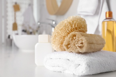 Natural loofah sponges and towel on table in bathroom. Space for text