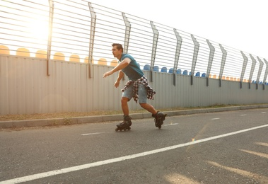Handsome young man roller skating outdoors. Recreational activity