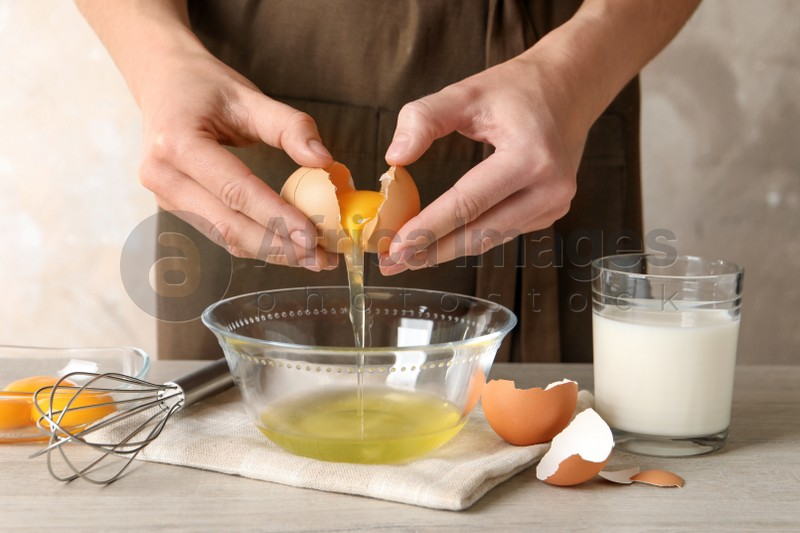 Woman separating egg yolk from white over glass bowl at light wooden table, closeup