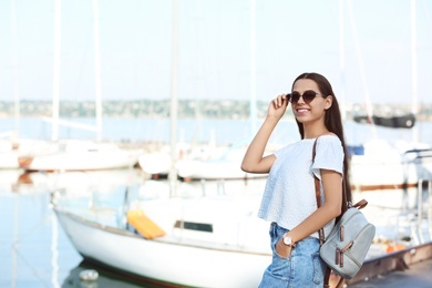 Young hipster woman in jean skirt on pier