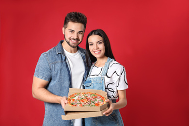 Happy young couple with pizza on red background