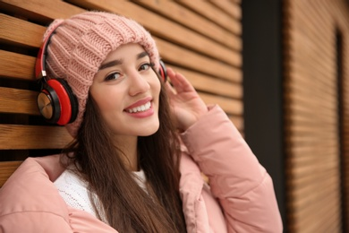 Young woman listening to music with headphones near wooden wall. Space for text