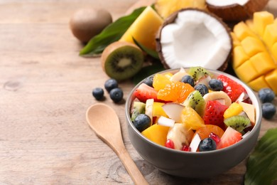 Bowl of delicious fruit salad on wooden table, space for text